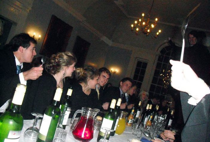 The Hatfield dining room in use at a college formal dinner. The students in this photo are spooning, a college tradition where the undergraduate students call the members of the Senior Common Room to dinner by banging their spoons on the table to different rhythms.