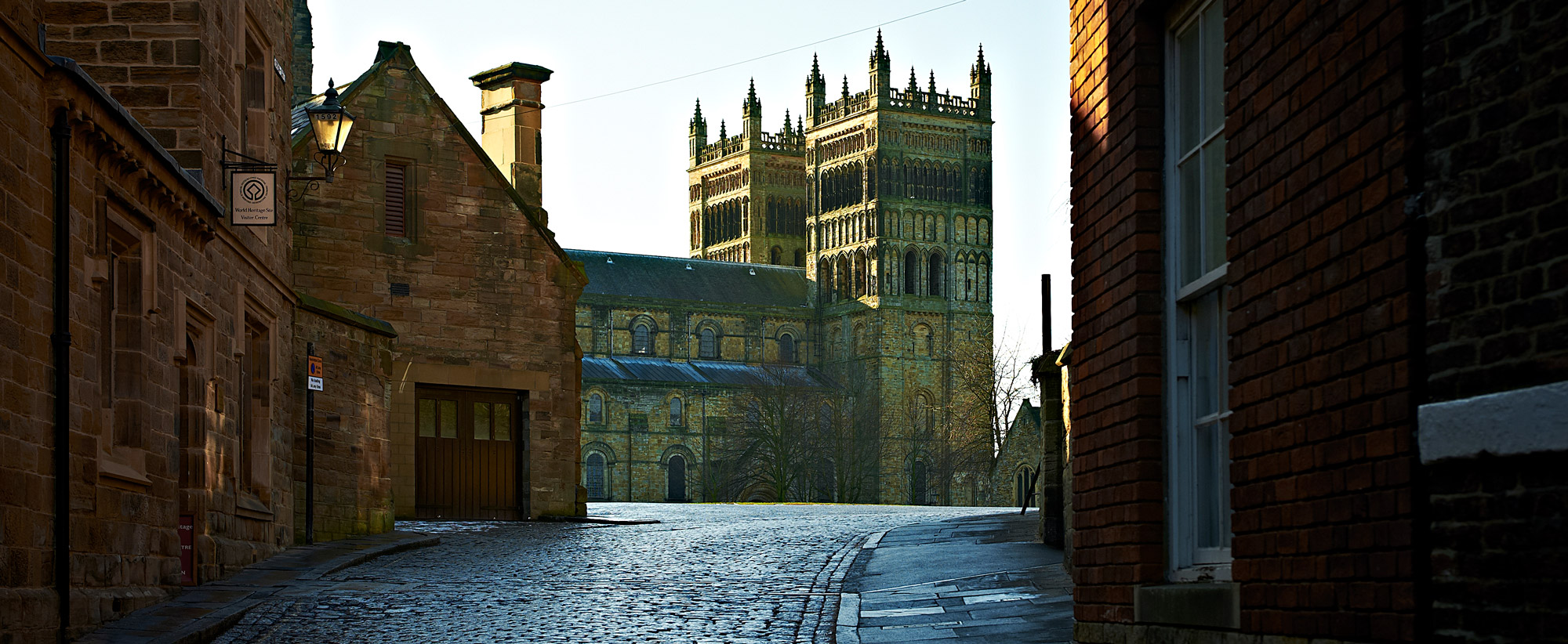 Photograph looking up a narrow cobbled street towards Durham Cathedral