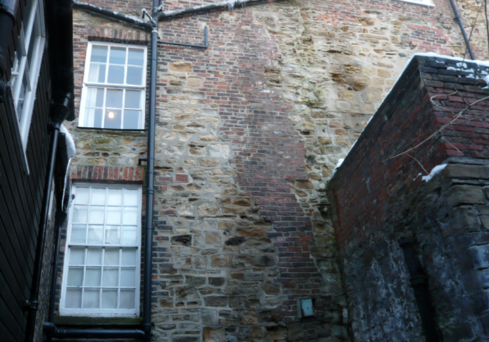 This image shows the back of a building on Owengate that was built along the line of the Castle walls and incorporates their remains in its construction. All the stonework is medieval, while the brickwork is from around 1800.