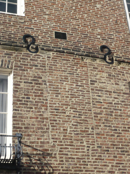 This blocked window on North Bailey indicates a change of use. Many of the buildings on this street started life as residential structures, but now house Durham University Departments. The iron s-shapes on the facade are structural braces, added to the building at some point to control movement or subsidence of the walls.