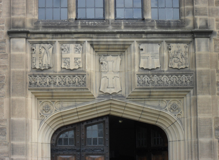 Detail of the facade showing (from left to right) the coats of arms of Van Mildert, the Prince Bishop who founded Durham University; the Bishopric of Durham, Durham University, the City of Durham. The coat of arms to the far right is yet to be identified.