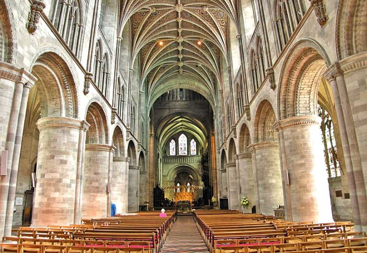 The nave of Hereford Cathedral showing the rounded arches of the Norman period above which are the pointed arches and elaborate rib vaulting of 14th century Gothic.