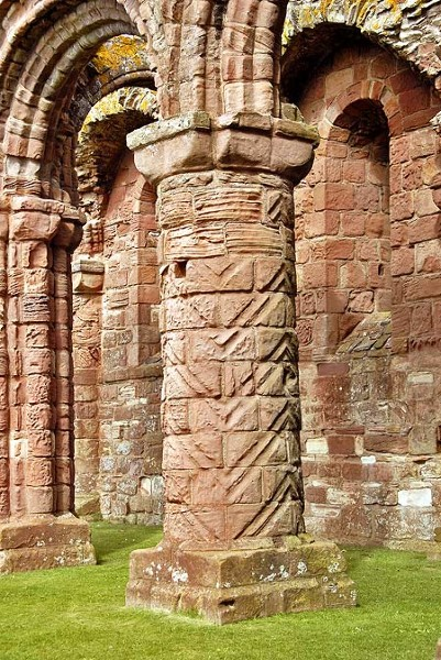 A pillar at Lindisfarne Priory, showing the chevron or zigzag design, which is also seen on the pillars of Durham Cathedral. As the priory was built by the Durham-based community of St. Cuthbert after the construction of the cathedral, it is likely that the same masons worked on both buildings, hence explaining the similarities.