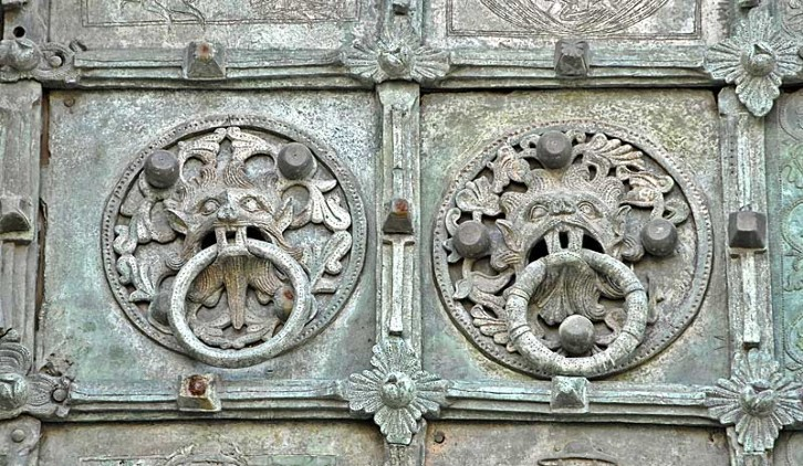 The Bronze door of Troia Cathedral was made by Oderiso di Benevento in 1119. The ringed bosses seen here may not have had the same significance as Durham Cathedral's Sanctuary Knocker, seen in the next image, but they are visually similar.