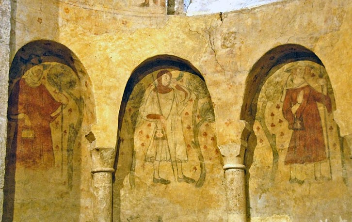 Eleventh century apse in the priory of Villeneuve d'Aveyron in France, decorated with fourteenth century scenes of pilgrims, a reminder of the role such buildings played.